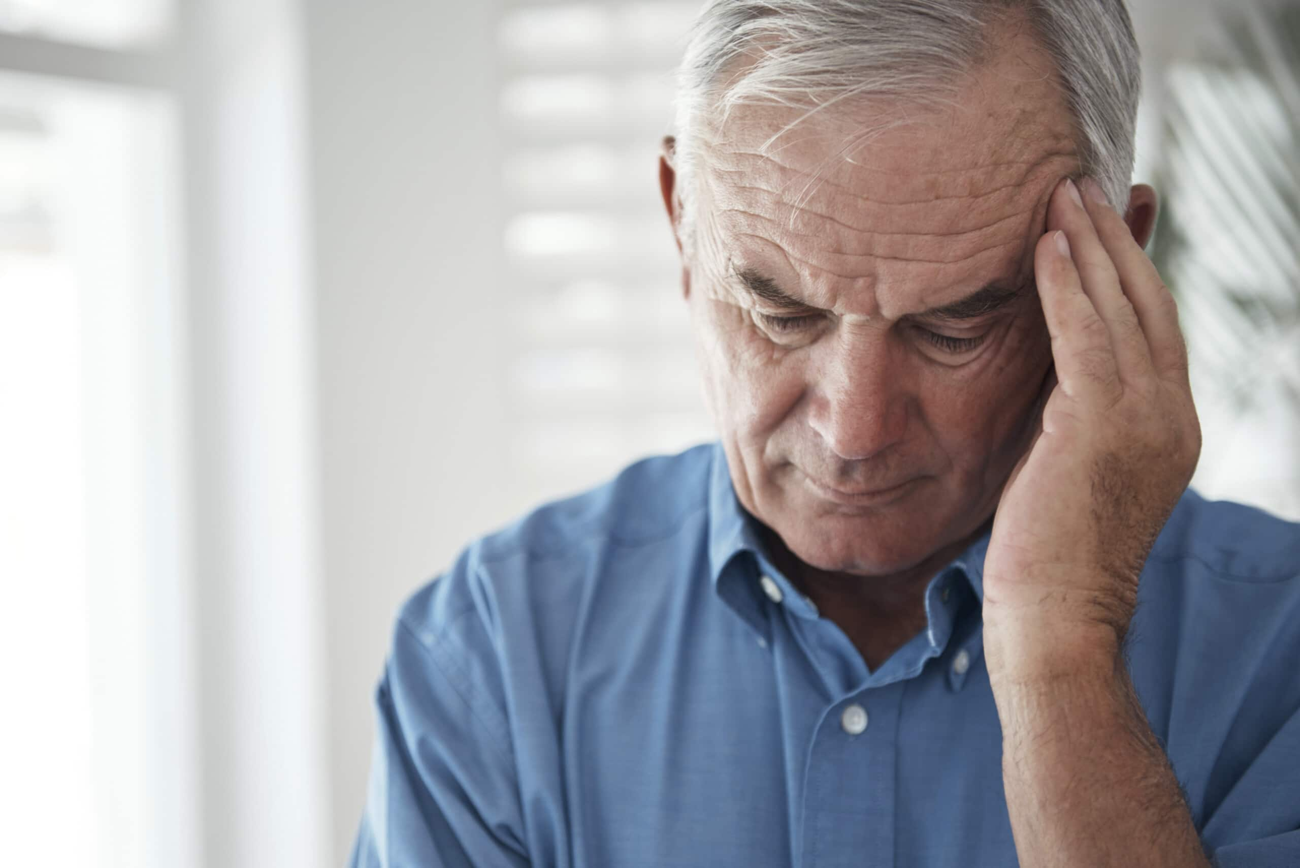 Older man rubbing forehead in pain