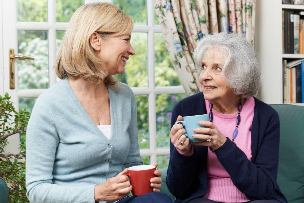 Woman having tea with her senior