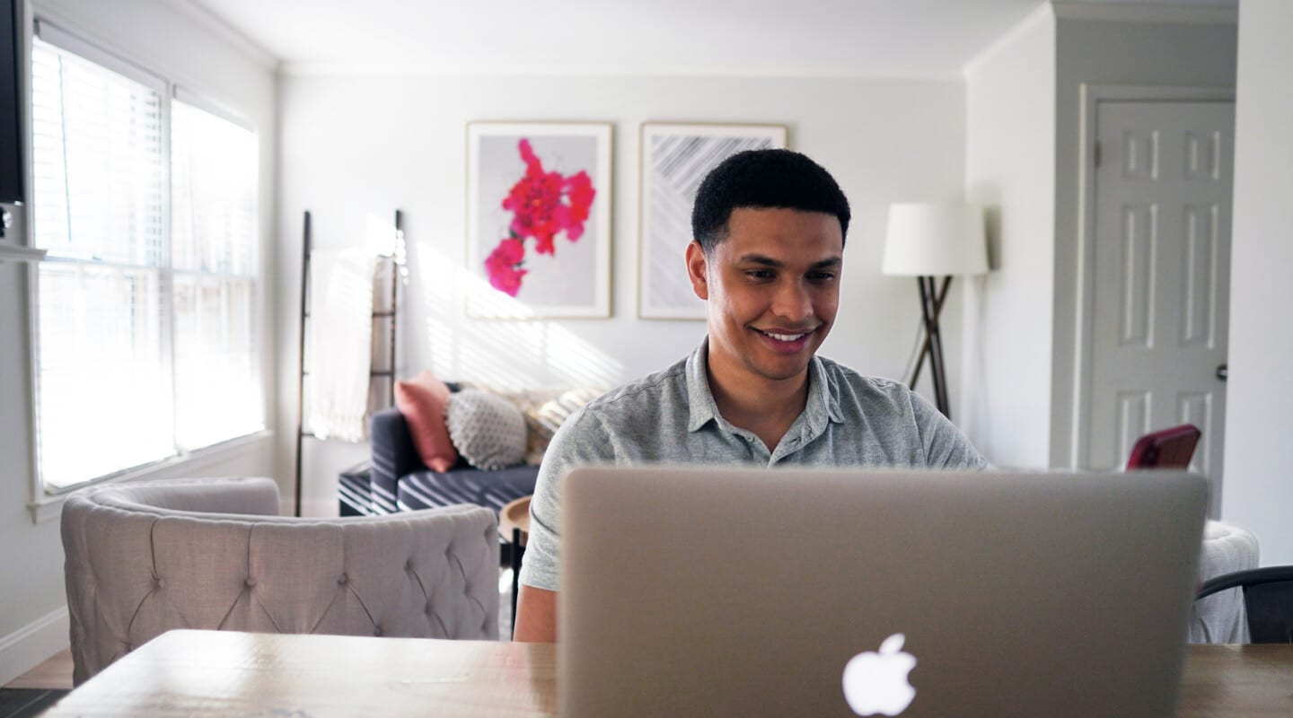 Man looking at the screen of his laptop and smiles
