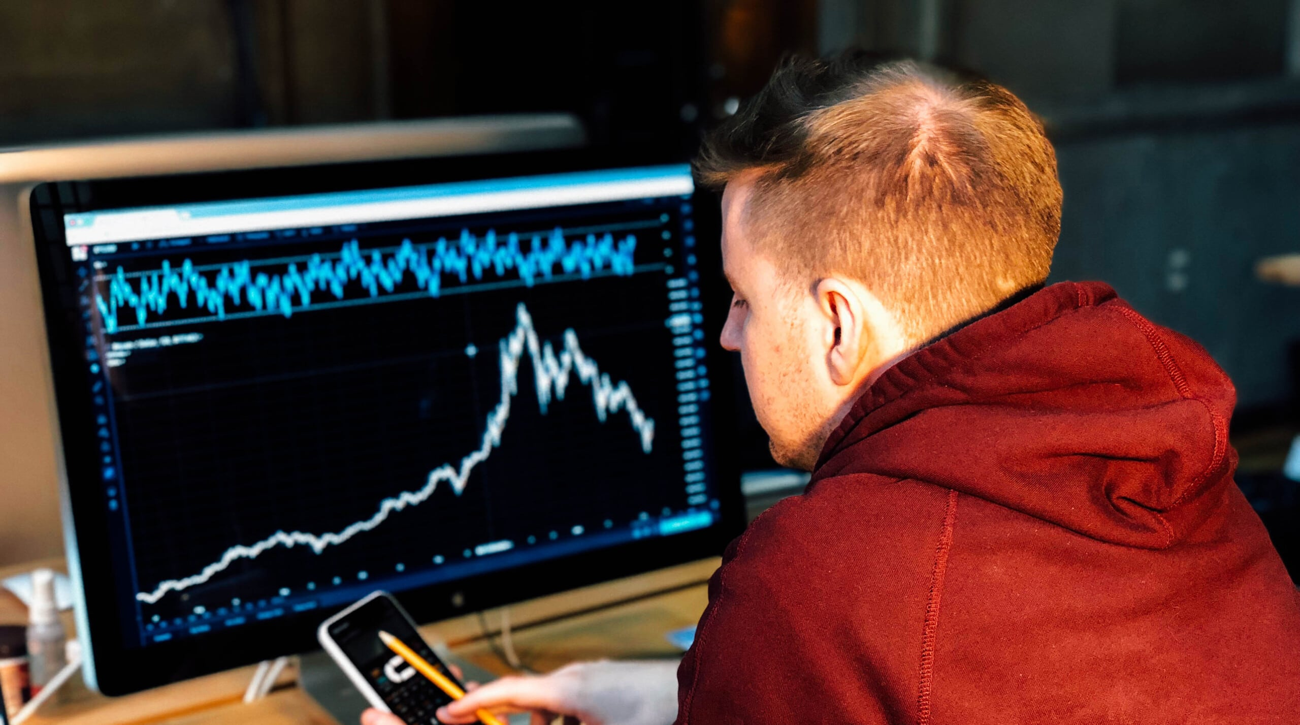 man looking at his phone with stock exchange graphs